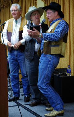 "Randy Boone accepts his ""Gathering of Guns 3"" from emcee John Buttram and festival co-sponsor Ray Nielsen."