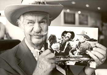 Tex Ritter sidekick Slim Andrews holds up a photo of he and Tex in their younger film-making days.