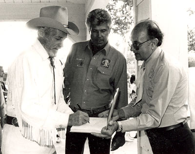 Guy Madison signs an autograph for a fan at the Golden Boot Awards in 1986. Jim Roberts of Mississippi, who for years sponsored the annual Pre-Boot party at Sportsmen's Lodge on Ventura Blvd. in Studio City, CA, is in the middle.