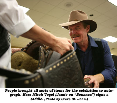 "People brought all sorts of items for the celebrities to autograph. Here Mitch Vogel (Jamie on ""Bonanza"") signs a saddle.  (Photo by Steve St. John.)"