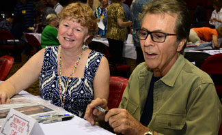 Festival registration desk volunteer Fliss Bonello lends a helping hand to James Darren.