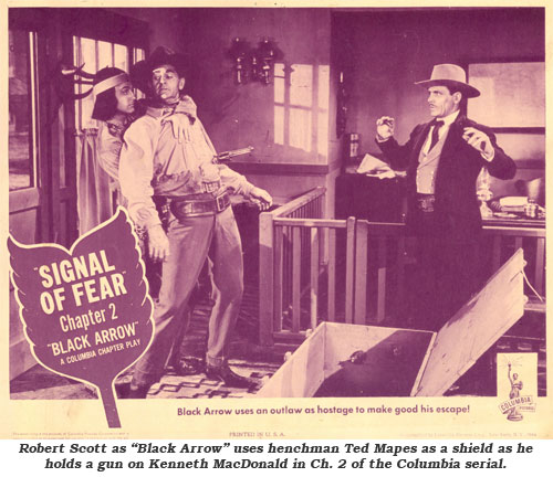 "Robert Scott as ""Black Arrow"" uses henchman Ted Mapes as a shield as he holds a gun on Kenneth MacDonald in Ch. 2 of the Columbia serial."