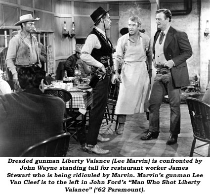 "Dreaded gunman Liberty Valance (Lee Marvin) is confronted by John Wayne standing tall for restaurant worker James Stewart who is being ridiculed by Marvin. Marvin's gunman Lee Van Cleef is to the left in John Ford's ""Man Who Shot Liberty Valance"" ('62 Paramount)."