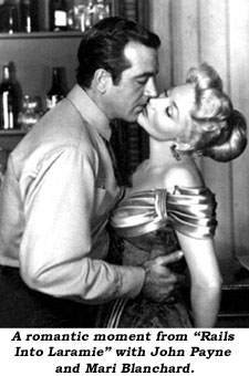 "A romantic moment from ""Rails Into Laramie"" with John Payne and Mari Blanchard."