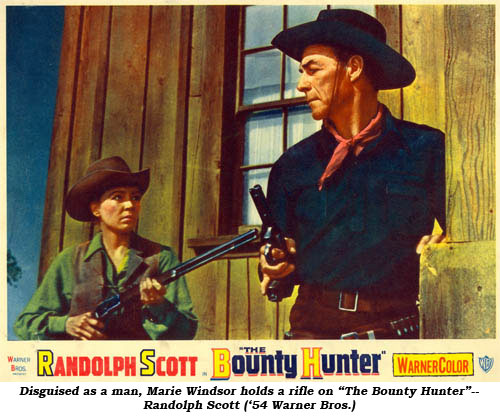 "Disguised as a man, Marie Windsor holds a rifle on ""The Bounty Hunter""--Randolph Scott ('54 WB)."