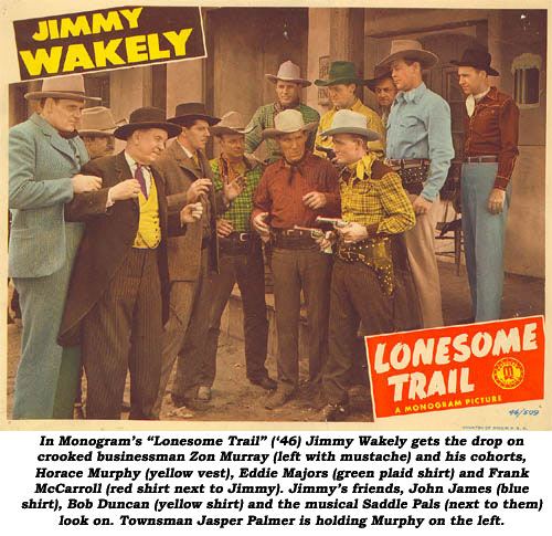 "In Monogram's ""Lonesome Trail"" ('46) Jimmy Wakely gets the drop on crooked businessman Zon Murray (left with mustache) and his cohorts, Horace Murphy (yellow vest), Eddie Majors (green plaid shirt) and Frank McCarroll (red shirt next to Jimmy). Jimmy's friends, John James (blue shirt), Bob Duncan (yellow shirt) and the musical Saddle Pals (next to them look on. Townsman Jasper Palmer is holding Murphy on the left."