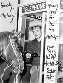 Will Hutchins in phone booth holds phone out to horse Penny.