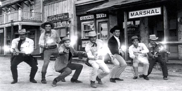 The Warner Bros. cowboys pose on lot: Wayde Preston, Ty Hardin, Jack Kelly, John Russell, James Garner, Peter Brown, Will Hutchins.