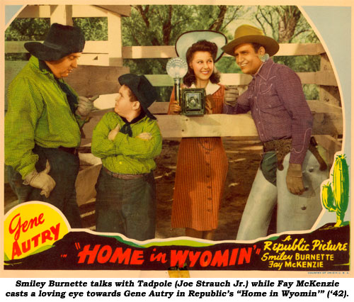 "Smiley Burnette talks with Tadpole (Joe Strauch Jr.) while Fay McKenzie casts a loving eye towards Gene Autry in Republic's ""Home in Wyomin'"" ('42)."