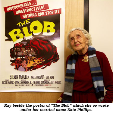"Kay beside the poster of ""The Blob"" which she co-wrote under her married name Kate Phillips."