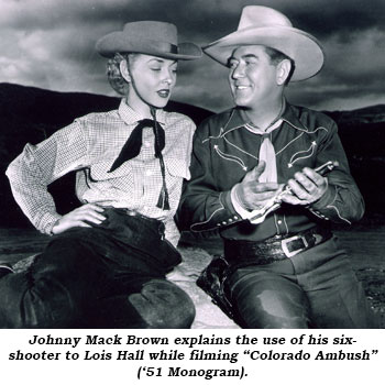 "Johnny Mack Brown explains the use of his six-shooter to Lois Hall while filming ""Colorado Ambush"" ('51 Monogram)."