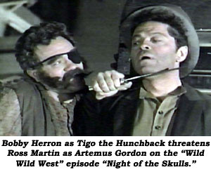 "Bobby Herron as Tigo the Hunchback threatens Ross Martin as Artemus Gordon on the ""Wild Wild West"" episode ""Night of the Skulls""."