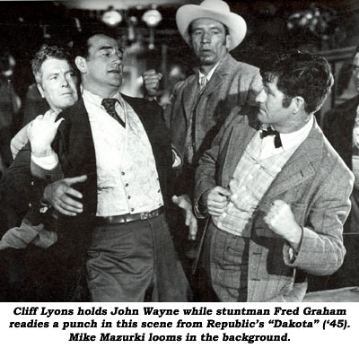"Cliff Lyons holds John Wayne while stuntman Fred Graham readies a punch in this scene from Republic's ""Dakota"" ('45). Mike Mazurki looms in the background."
