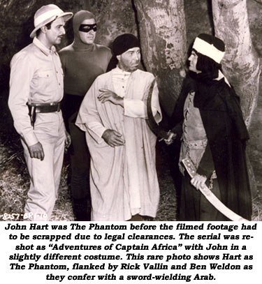 "John Hart was The Phantom before the filmed footage had to be scrapped due to legal clearances. The serial was reshot as ""Adventures of Captain Africa"" with John in a slightly different costume. This rare photo shows Hart as The Phantom, flanked by Rick Vallin and Ben Weldon as they confer with a sword-weilding Arab."