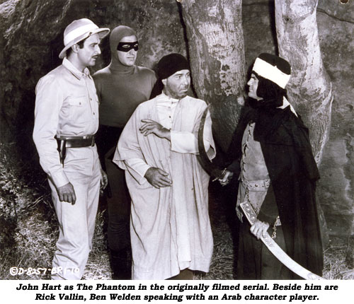 John Hart as The Phantom in the originally filmed serial. Beside him are Rick Vallin, Ben Welden speaking with an Arab character player.