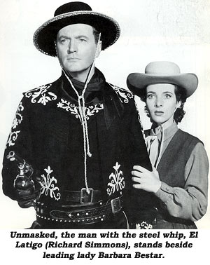 Unmasked, the man with the steel whip, El Latigo (Richard Simmons), stands beside leading lady Barbara Bestar.