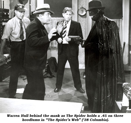 "Warren Hull behind the mask as The Spider holds a .45 on three hoodlums in ""The Spider's Web"" ('38 Columbia)."