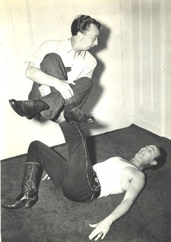 "Roy Rogers gets a little ""exercise"" from contortionist Emmett Oldfield"