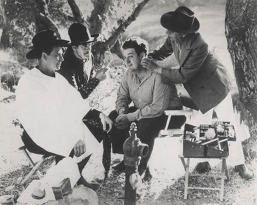 "Smiley Burnette and Bob Livingston get made up for a scene in Republic's ""Pride of the Plains"" ('44) while Harry Woods visits the set from another picture as he was not in ""Pride of the Plains"". Livingston, who wore a white hat in the short-lived series, had to don his old Stony Brooke costume...black hat and two-tone pants...for part of the film to match stock footage from ""Hit the Saddle"". (Thanx to John Brooker.)"