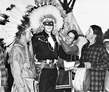 Radio's Lone Ranger, Brace Beemer, poses wearing a feathered head dress with the chief of the Chippewa Nation and other tribe members during the 49th annual Indian Fair in 1946. (Photo courtesy Roy Bonario.)