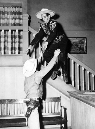 The camera catches Duncan Renaldo as the Cisco Kid mid-air-stunt into the arms of a waiting stuntman/heavy.