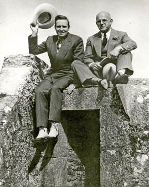 Gene Autry and Republic President Herbert J. Yates sit atop a pillbox in England while Gene was on tour.