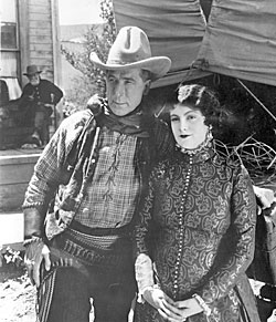 "William S. Hart and leading lady Barbara Bedford pose for the camera while making ""Tumbleweeds"" ('25)."