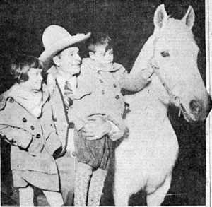 World's Champion Cowboy Yakima Canutt with two fans as he headlined the World's Show Sensations sponsored by the Toledo, OH Shrine club in January 1930.
