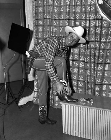 Gene Autry puts on his spurs for a photo shoot. (Thanx to Billy Holcomb.)