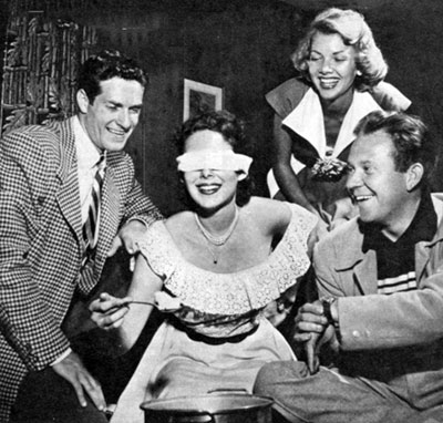 Party time in 1951 Hollywood. (L-R) Hugh O'Brian, Vanessa Brown, Barbara  Lawrence and Dick Erdman. The game they're playing involves a timed effort by a blindfolded contestant to pick up scattered pieces of cotton with a spoon and deposit them in a large pot.