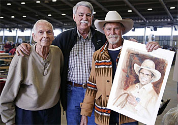 """Gunsmoke""—Buck Taylor holds up his self portrait for two buyers."