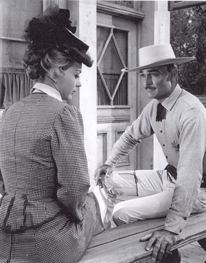 "Actress Jan Shepard and ""Lawman"" John Russell take a break between scenes. Note the cigarette in John's hand."