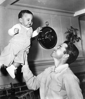 "Audie Murphy holds high not quite 2 year old son, James ""Skipper"" Shannon, in 1956."