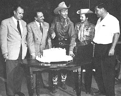 Roy Rogers celebrates 12 years at Republic. Dale Evans and director Bill Witney  are on the right.
