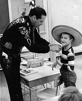 During the 12th annual Shrine Showdeo at the Minnesota State Fair, Duncan Renaldo, the Cisco Kid, makes a young fan very happy by letting him try on his sombrero. (Thanx to Terry Cutts.)