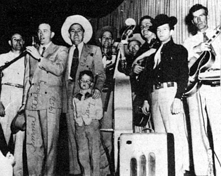 Cal Shrum (white hat, center) and son Gary welcome guest star Jimmy Wakely to Shrum's Saturday night show which in the '50s originated in Albuquerque, New Mexico.
