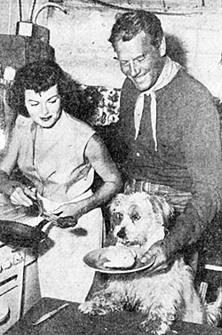 "In between scenes for Universal's ""Lone Hand"" ('52) co-stars Barbara Hale and Joel McCrea cater to the hunger of dog actor Butch."