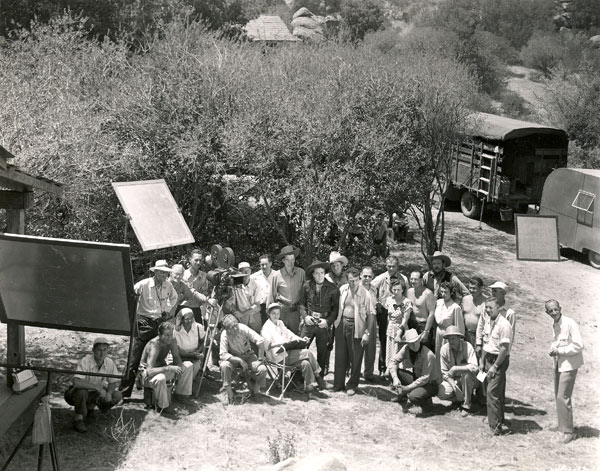 "Cast and crew of ""Frontier Revenge"" ('48) assemble on Iverson's Ranch for a group photo. Lash LaRue dead center, to his right is Jim Bannon. Is that producer Ron Ormond to Lash's left, shirt open? Director Ray Taylor and most likely script supervisor Moree Herring are seated to Lash's right. Co-stars Ray Bennett and Lee Morgan are in the back to Lash's left. Others unidentified. Can anyone help? Cute to notice the kids looking on while hiding in the bushes. Obviously missing from the cast foto are Fuzzy St. John, Peggy Stewart and Sarah Padden."