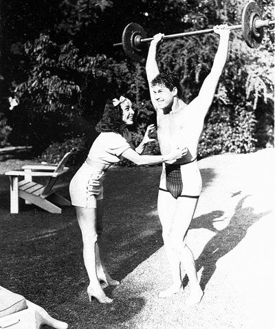"A pre-Lone Ranger Clayton Moore seems to be saying to Lupe Velez, ""Don't tickle me while I've got this barbell."" (Thanx to John Bickler.)"