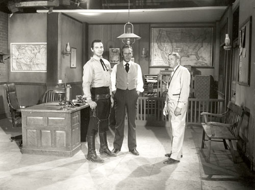 "Pat Conway as Sheriff Clay Hollister and Richard Eastham as TOMBSTONE EPITAPH editor Harris Claybourne on the set of the sheriff's office for ABC's ""Tombstone Territory"". The other man could be a director or even the set decorator."