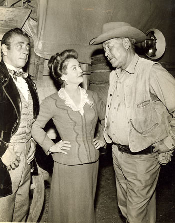 "Robert Strauss, Bette Davis and Ward Bond as wagonmaster Major Seth Adams during a lull in shooting for ""The Elizabeth McQueeney Story"" episode of NBC's ""Wagon Train"" in 1959."