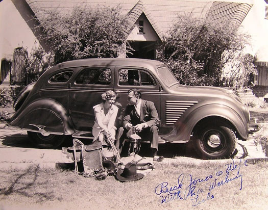 "The caption reads ""Buck Jones and wife [Dell] with his working tools [saddle, rope, hat, bridle, etc.]."" Taken in front of Buck's home. (Can anyone identify the make and year of Buck's car?) (Thanx to Bobby Copeland.)"
