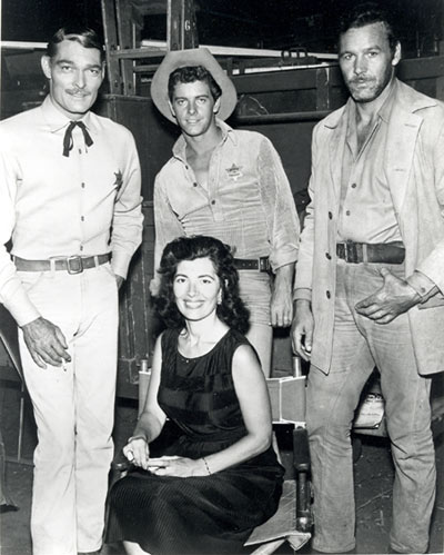 "Taking a break between scenes of Warner Bros.' ""Lawman"" are John Russell, Peter Brown, badman Chris Alcaide and his wife Peri Alcaide, a noted foreign corespondent. Note the cigarette in Russell's hand."