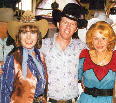 Stuntman Neil Summers surrounded by beauty--Penny Edwards (left) and Vera Hruba Ralston (right) at a Monte Hale birthday party in 1979.