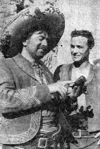 "Rico Alaniz (left) points out the notches on the grip of his gun to Robert Loggia who plays the lead in Disney's ""Nine Lives of Elfego Baca"". Photo taken on location in Cerrillos, New Mexico, in June 1958."