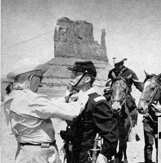 "John Ford adjusts Pat Wayne's wardrobe before a ""Searchers"" scene in Monument Valley."