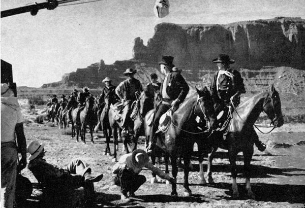 "John Ford (seated) directs a sheriff's posse scene with Ward Bond and John Wayne in the lead for ""The Searchers""."