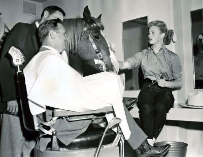 It's back in the make-up chair again for both Gene Autry and his wonder horse Champion.