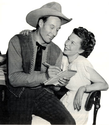 1947 publicity shot of Bill Elliott in a role reversal pose as he jots down dictation from his business manager Sally Thro.