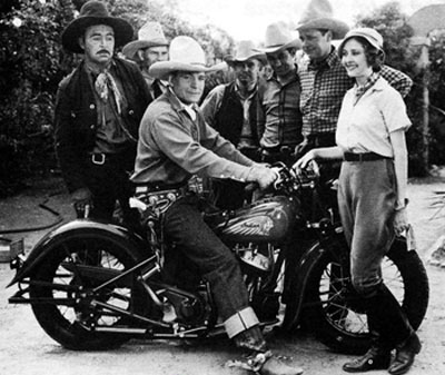 "Buck Jones is mighty proud of his new Indian motorcycle. Standing in front is ""Red Rider"" serial heroine Marion Shilling. Beside her in the checkered shirt is Ed Cobb. Photo taken in 1934 during the making of that Universal serial. (Photo courtesy Bobby Copeland.)"